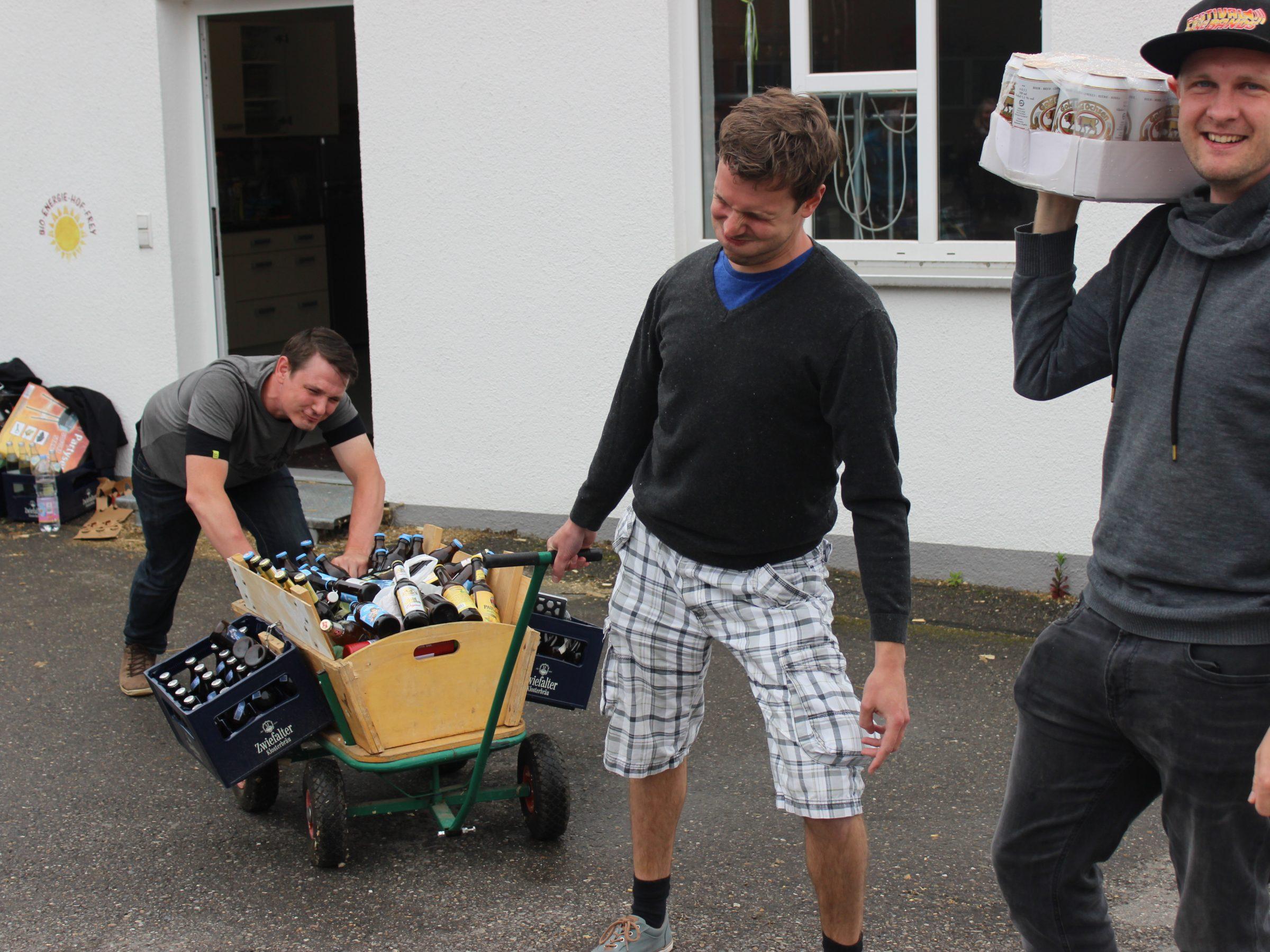 2 Männer schieben und ziehen einen schwerbeladenen wagen mit Bier. Daneben steht ein entspannter junger Mann der lässig eine Gold Ochsen Dosenbierpalette 24x0,5l auf der Schulter hat. Nicht schleppen, Coupon auf der Homepage kaufen und frisch gekühltes Dosenbier auf dem Festival bekommen :-)