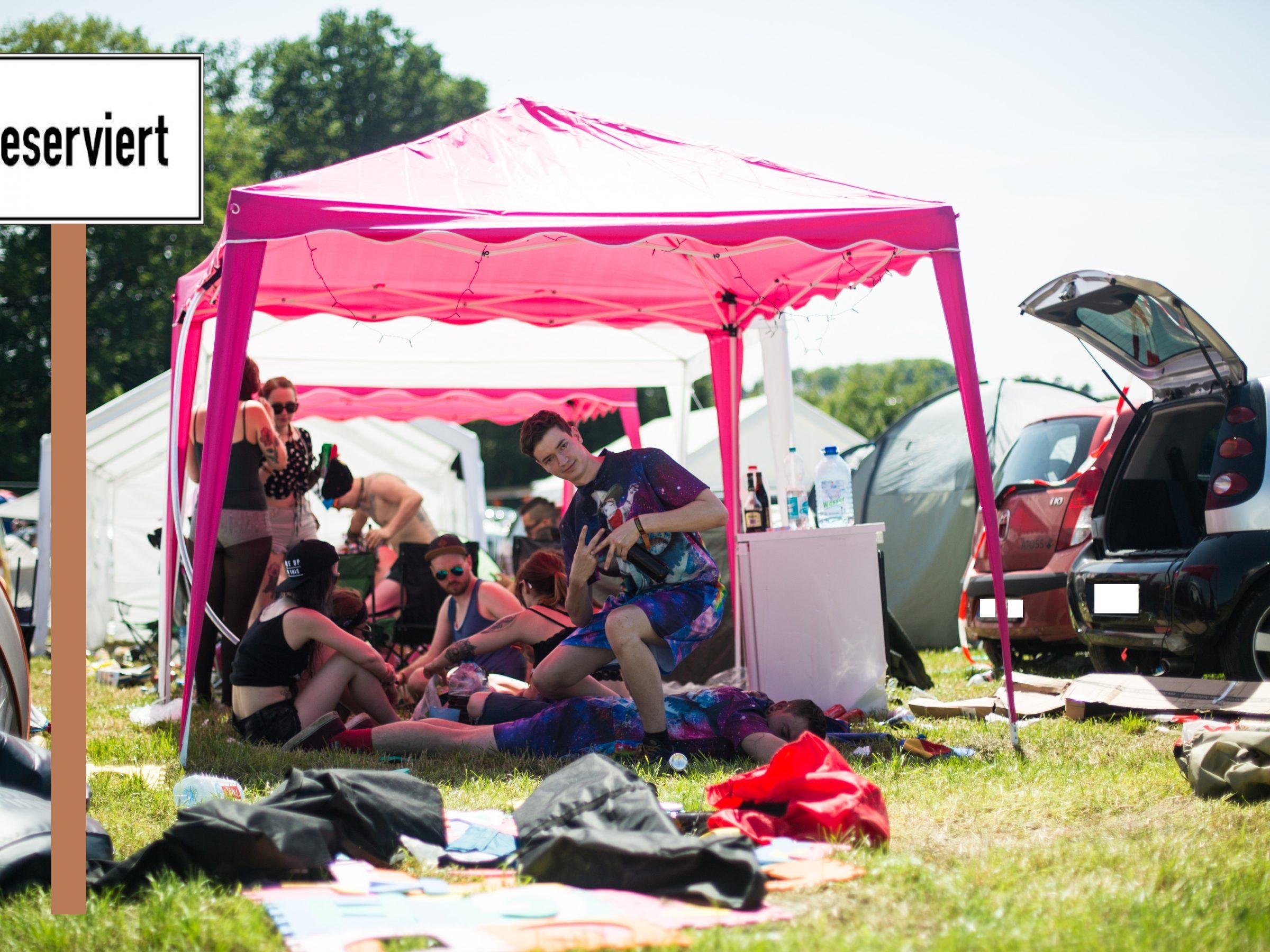 Bild zeigt einen Typischen Campingplatz beim Festival ohne Bands. Leute sitzen unter einem pinken Pavillon. Links steht ein Zelt und rechts Autos mit offenem Kofferraum. Dann steht dort noch ein Schild mit Reserviert
